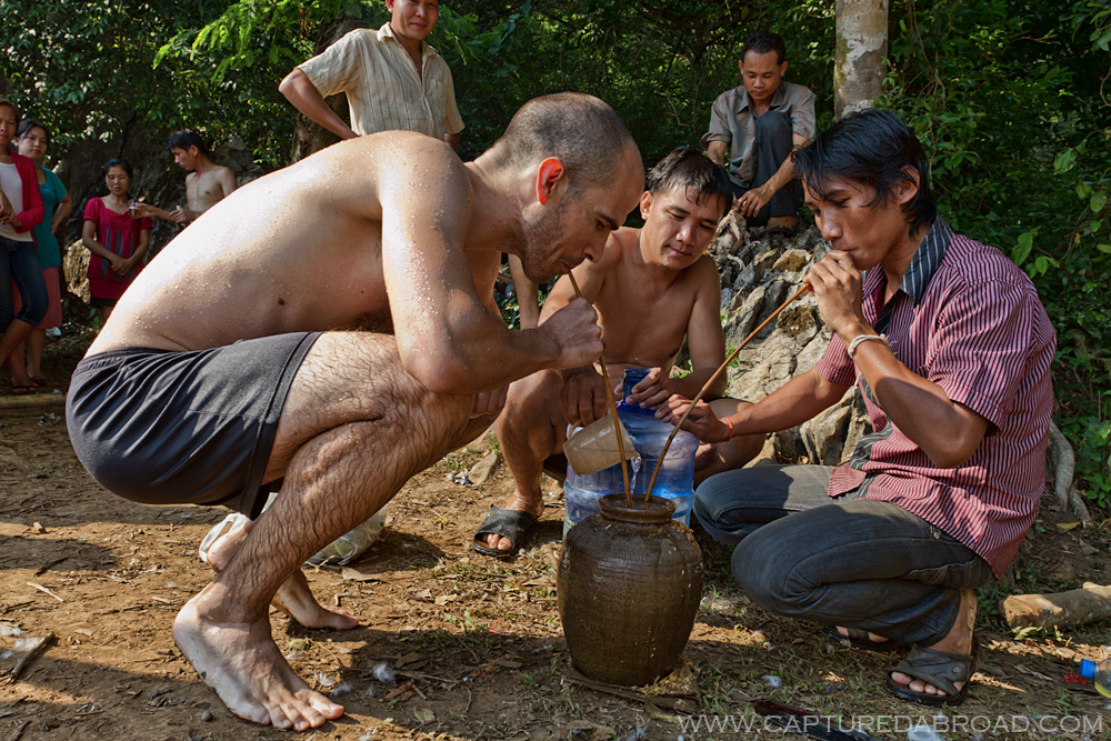 """Drinking Laohoi rice wine with locals at a cool spring in Bo Houay Namgen on the """"Thakhek loop"""""""