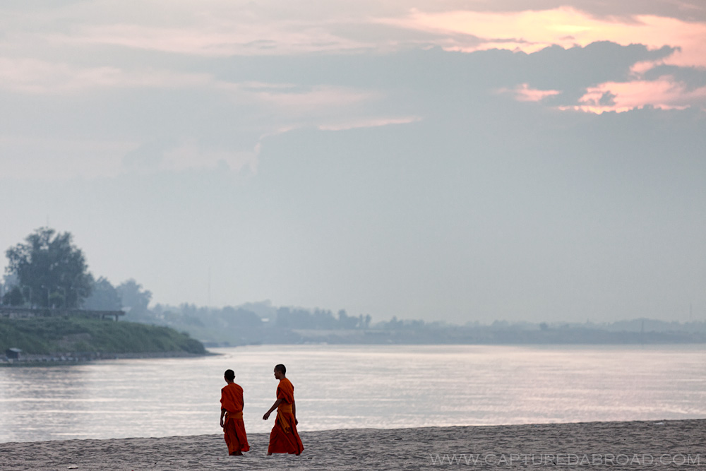 Monks walk on Don Chan bank of the Mekong river in Vientiane
