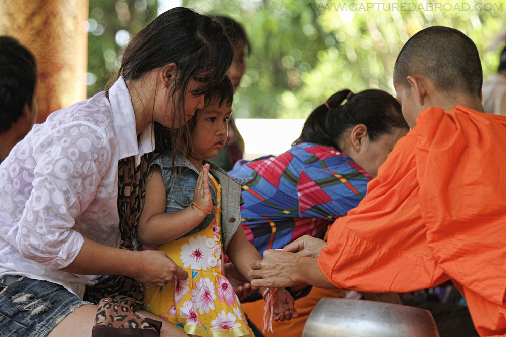 Pi Mai Celebrations in Vientiane, Laos, Monk puts wristband on girl