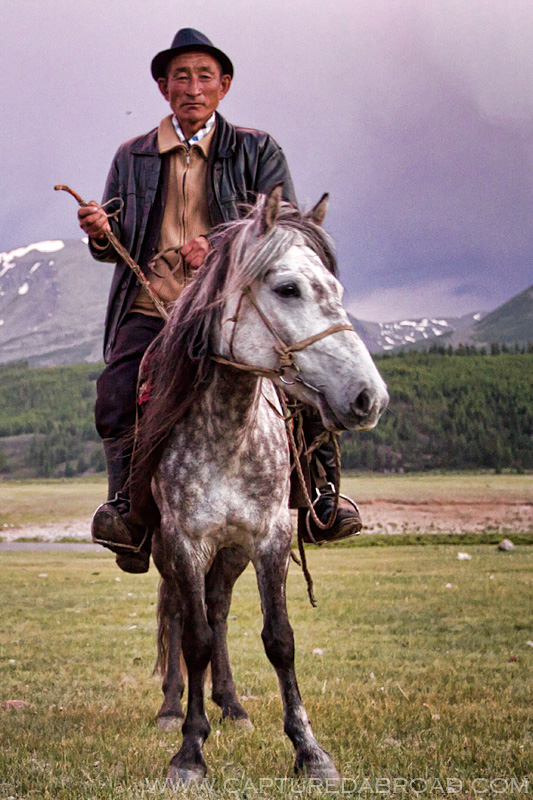 Man on a silver horse with a purple sunset in Mongolia Khurgan nuur