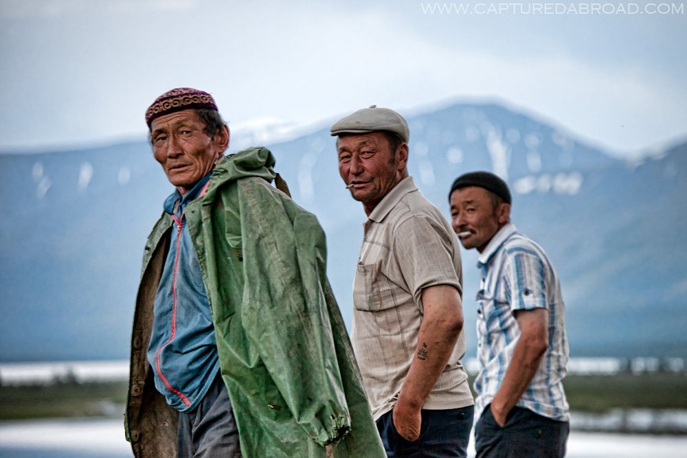 Three Kazak-mongol men walk along the Khurgan Nuur