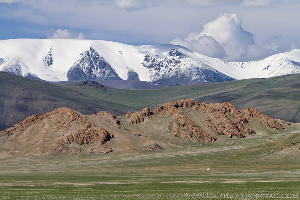 Bayan-Ölgii Province, snow capped mountains and fields of grass